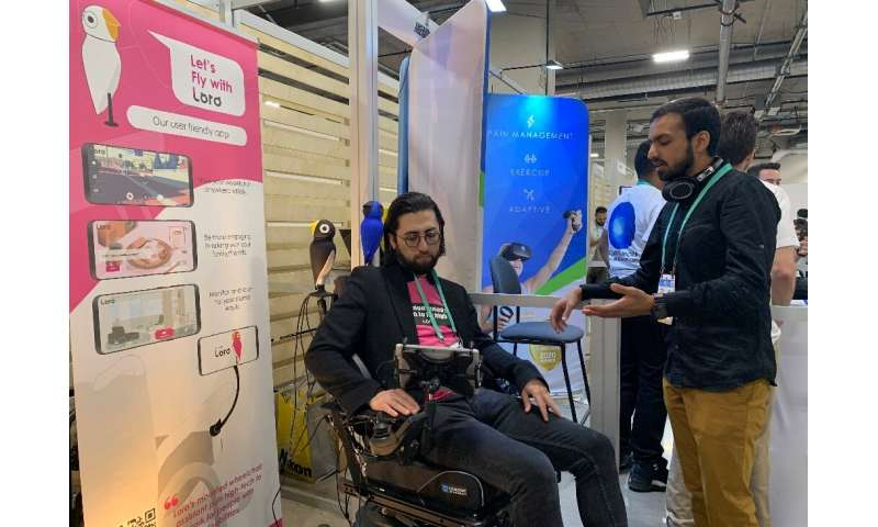David Hojah (L), cofounder and CEO of Loro, shows the robot assistant for the wheelchair-bound at the 2020 Consumer Electronics