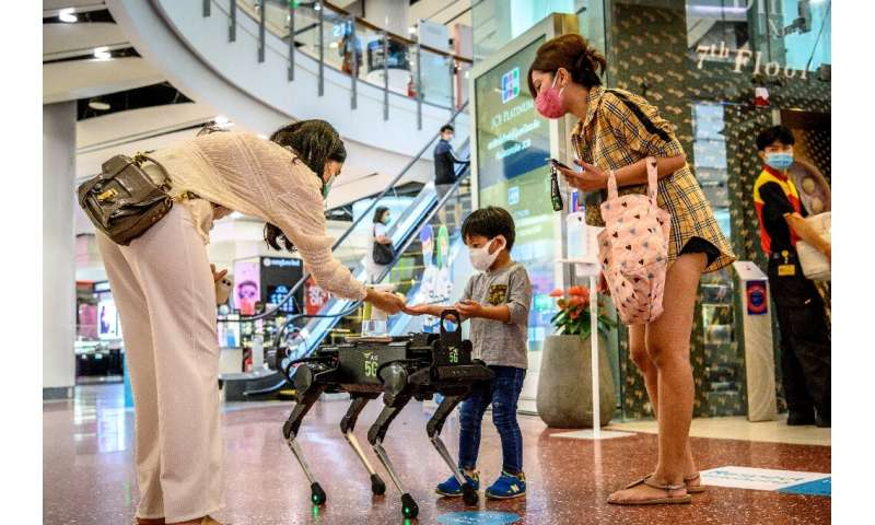 Don't be afraid: K9 doesn't bite, he distributes hand sanitiser to visitors in a shopping mall in Bangkok