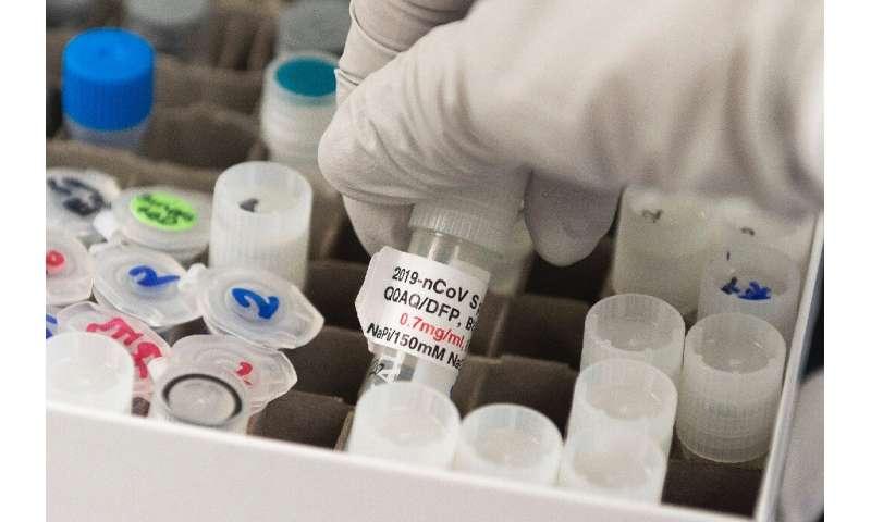 Dr. Nita Patel, Novavax director of antibody discovery and vaccine development, examines a vial of the company's experimental CO