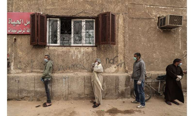 Egyptian men wait outside a centre of non-governmental organisation the Egyptian Food Bank to receive cartons with foodstuffs am