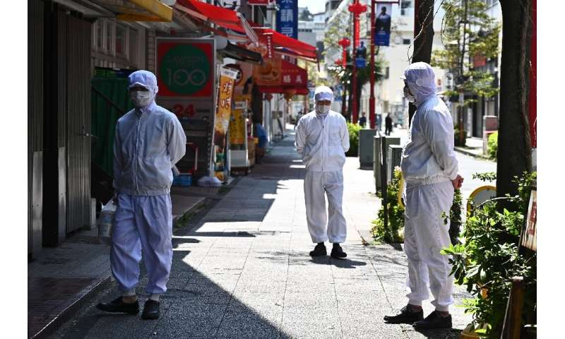 Employees of a restaurant wearing masks stand outside their eatery before it opens in the Chinatown area in Yokohama, Japan