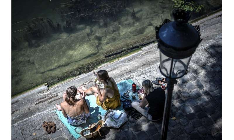 Europeans have thronged parks and rivers, as here on the banks of the River Seine in Paris, as the rising mercury announces the