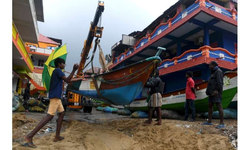 Fishermen move their boats as cyclone Nivar approaches the eastern Indian coast