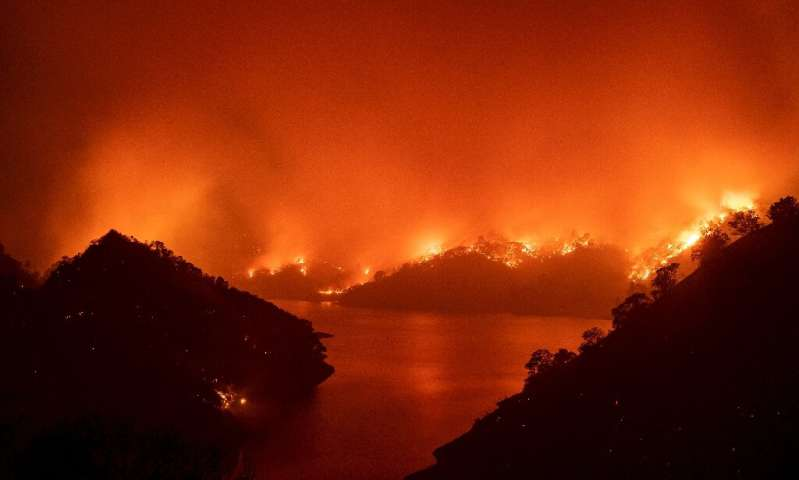 Flames surround Lake Berryessa during the LNU Lightning Complex fire in Napa, California on August 19, 2020