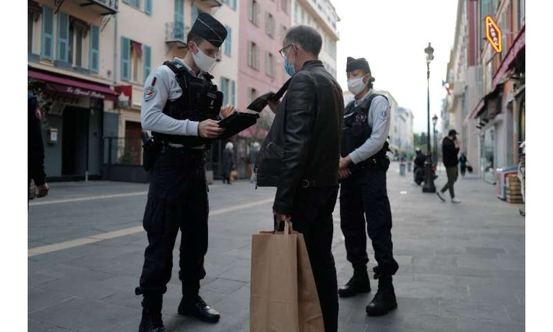 French police officers control passersby in Nice, during the country's second lockdown aimed at containing the spread of covid-1