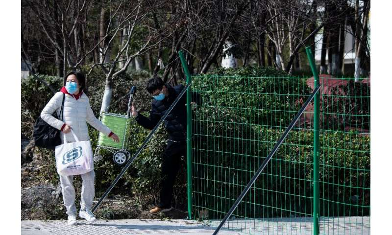 "Green fences and ""no entry"" signs block streets near the headquarters of Alibaba, in a city hit by China's deadly vira"