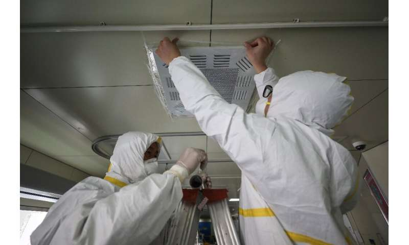 Hospital employees in Wuhan, China seal an airvent to prevent possible airborne transmission of the new coronavirus