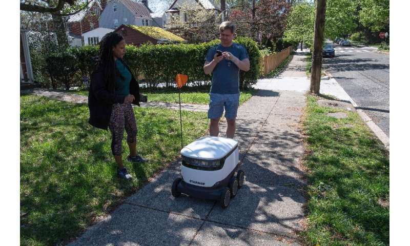 Kimmo Kartano uses his smartphone to open a food delivery robot from the Broad Branch Market grocery store as Audra Grant looks