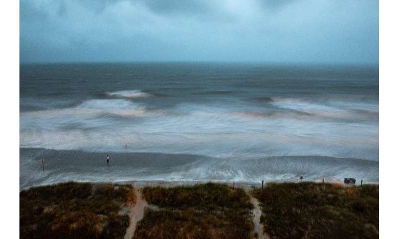 Large surf is swirled by the wind and captured by a long exposure, while a person stands on the shore as Hurricane Isaias approa