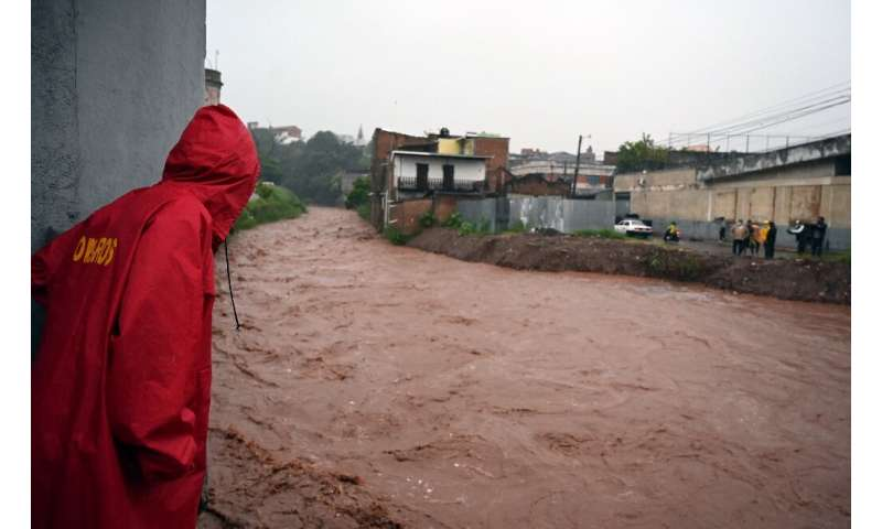 Locals look at the rising level of the Chiquito river, in La Hoya neighbourhood, in Tegucigalpa, following the passage of Hurric