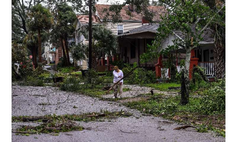 Mark Robinson removes tree branches outside his home in Pensacola, Florida