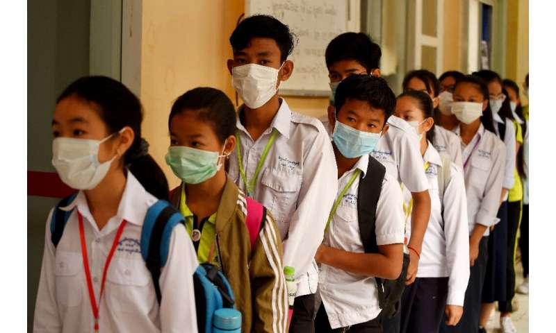 Masked Cambodian students line up to disinfect their hands with an alcohol solution before entering class at a school in Phnom P