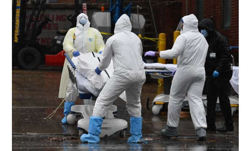 Medical personnel move a body to a refrigerated truck serving as a makeshift morgue at Brooklyn Hospital Center in New York
