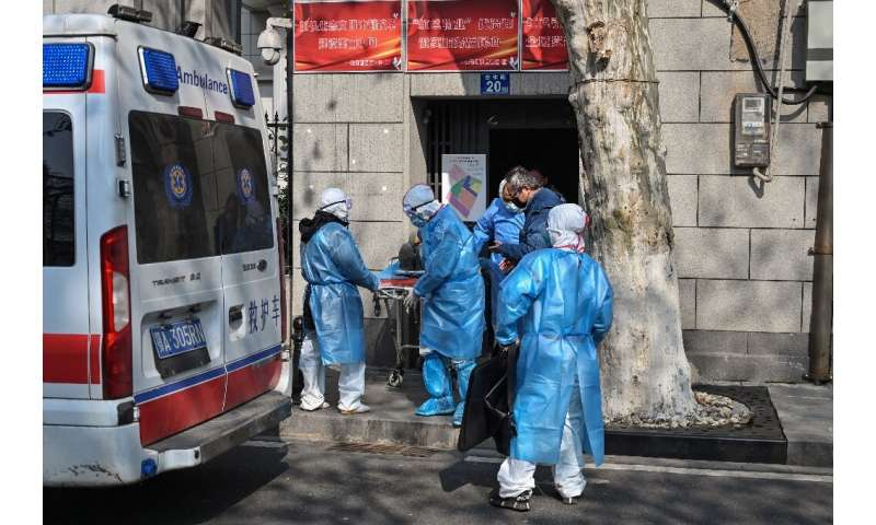 Medical staff in protective clothing carry a suspected virus patient from an apartment in Wuhan