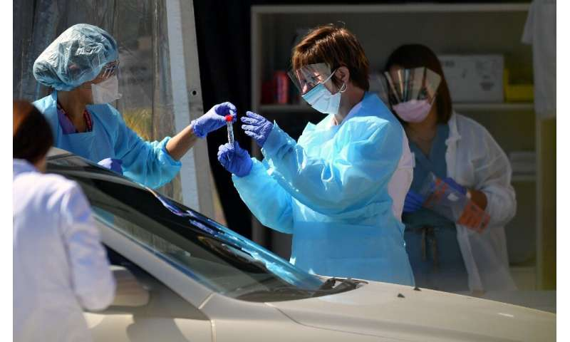 Medical workers at a Kaiser Permanente French Campus test a patient for the novel coronavirus, COVID-19, at a drive-thru testing
