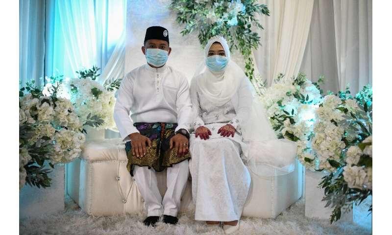 Mohammad Nor Azwan Ishak, 27, and Nuramiraalia Noorbashah, 25, wear face masks as a preventive measure against the novel coronav