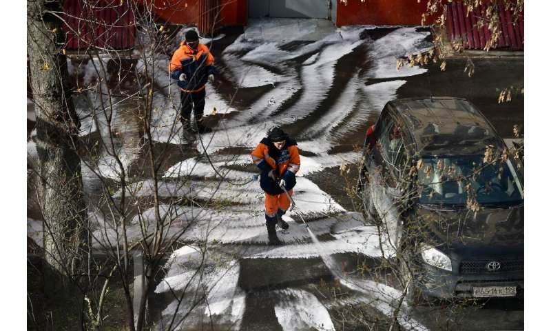 Municipal workers clean and disinfect walkways in a yard in Moscow, during the strict lockdown in Russia