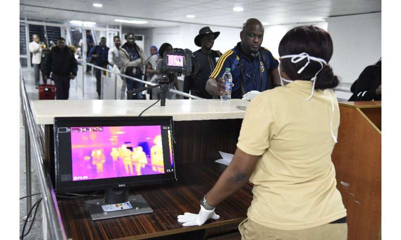 Passengers have their temperatures checked on arrival at the Murtala Mohammed International Airport in Lagos, Nigeria