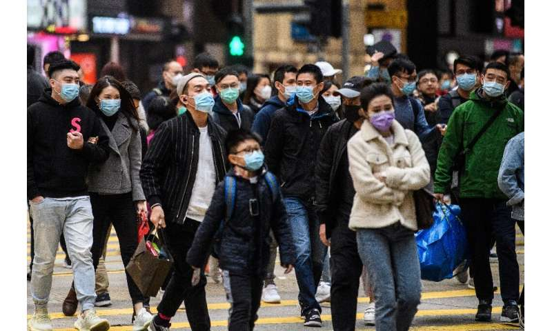 Pedestrians wearing face masks cross a road during a Lunar New Year of the Rat public holiday in Hong Kong on January 27, 2020,