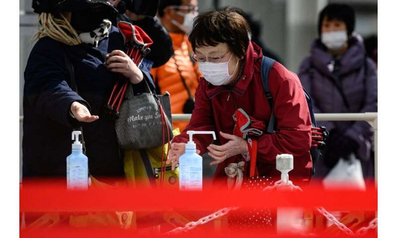People clean their hands with hand sanitiser in Fukushima, Japan