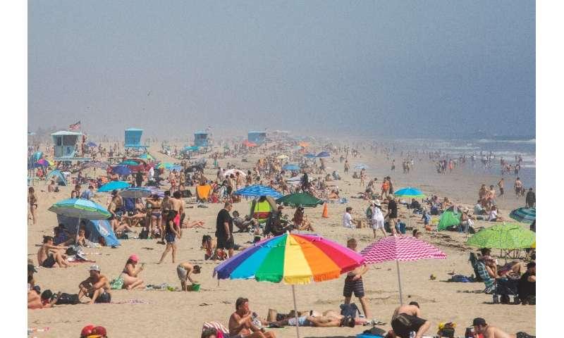 People enjoy the sun and sand amid the novel coronavirus pandemic in Huntington Beach, California