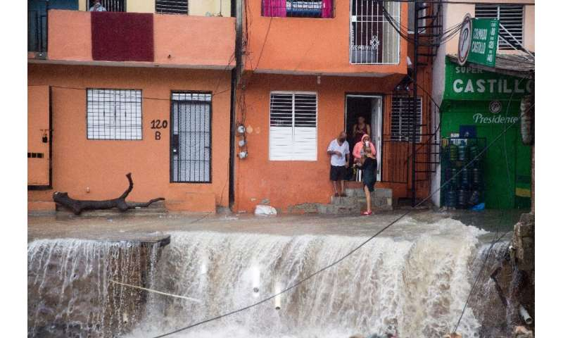 People look on as floodwaters from Storm Laura rips up streets in the Dominican Republic capital Santo Domingo