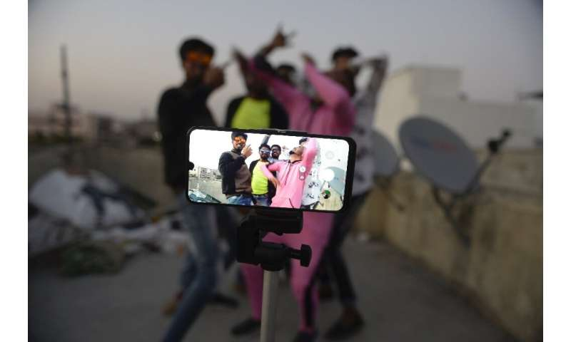 People pose while making a TikTok video on the terrace of their residence in India