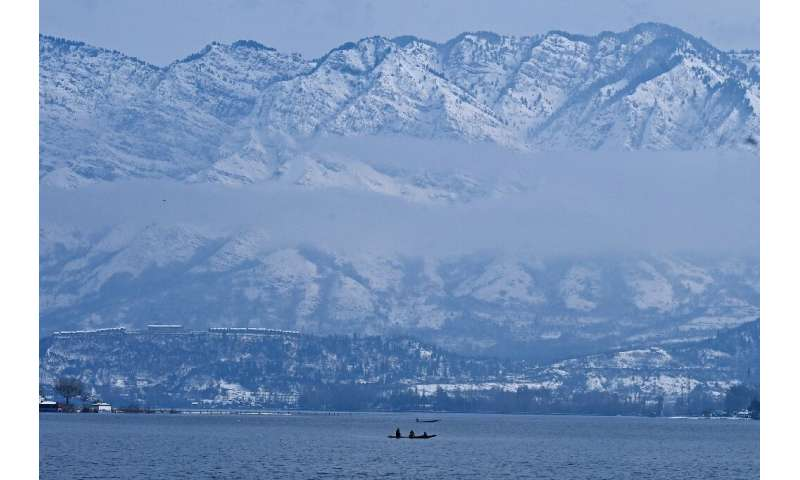 People ride on boats in the Dal Lake after heavy snowfall in Srinagar, Indian-administered Kashmir