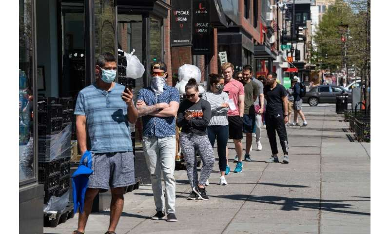 People stand in line to enter a grocery store in Washington, DC amid the coronavirus pandemic