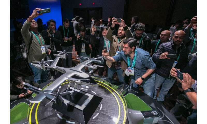 People take photos of a model of Hyundai's S-A1 electric vertical takeoff and landing (eVTOL) aircraft built in partnership with
