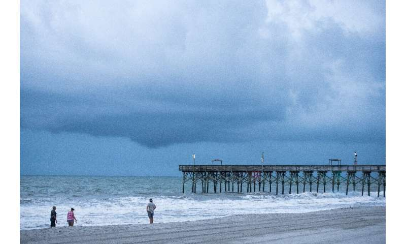 People walk along the beach in Myrtle Beach, South Carolina as Tropical Storm Isaias is set to strengthen into a hurricane and c