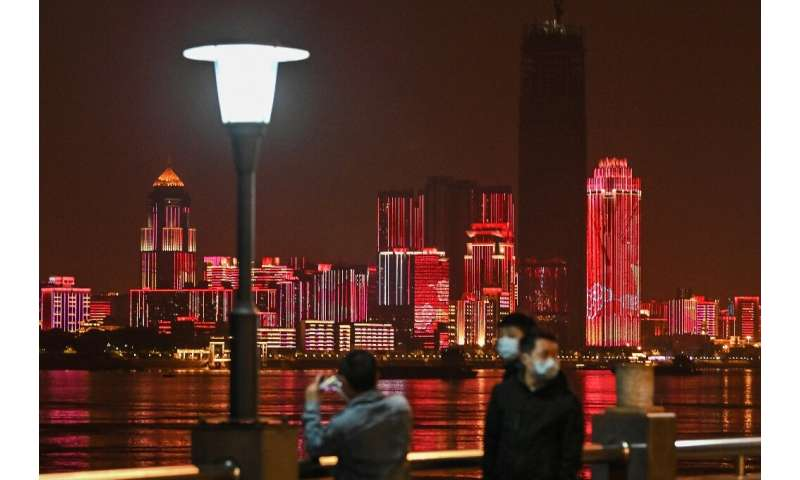 People wearing facemasks walk near the Yangtze River in Wuhan, epicentre of the coronavirus, which reported no new deaths from t