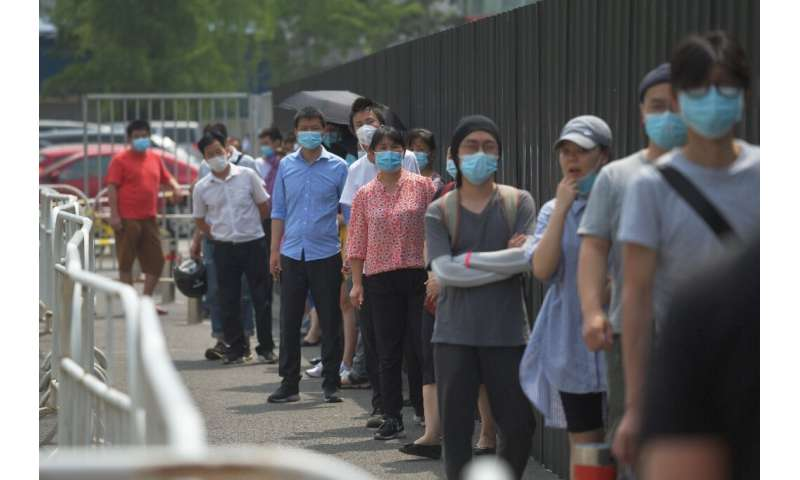 People wear masks as they wait in line to undergo COVID-19 swab tests at a testing station in Beijing
