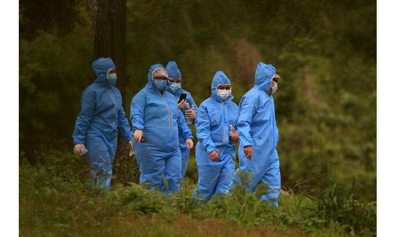 People wear protective suits while attending the burial of a loved one at the annex of the Jardin de Los Angeles cemetery where