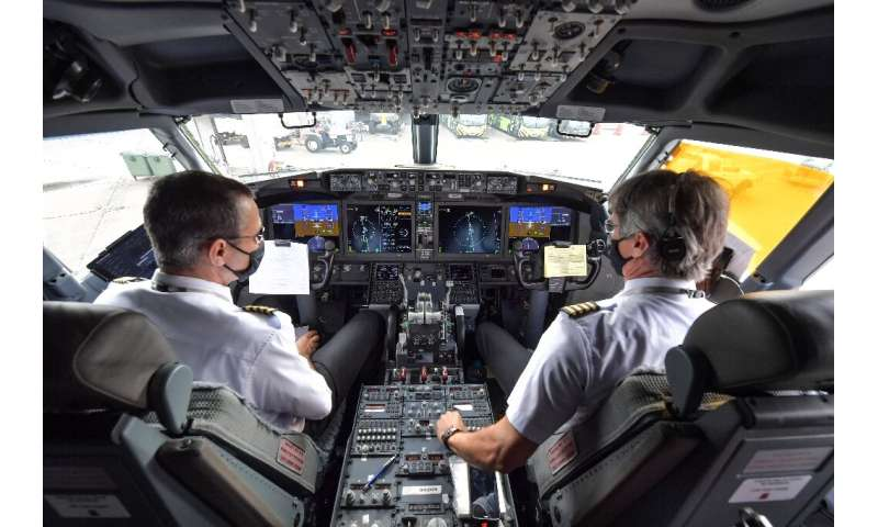 Pilots are shown in the cockpit of a Boeing 737 MAX airliner operated by the low-cost airline Gol while on the runway before