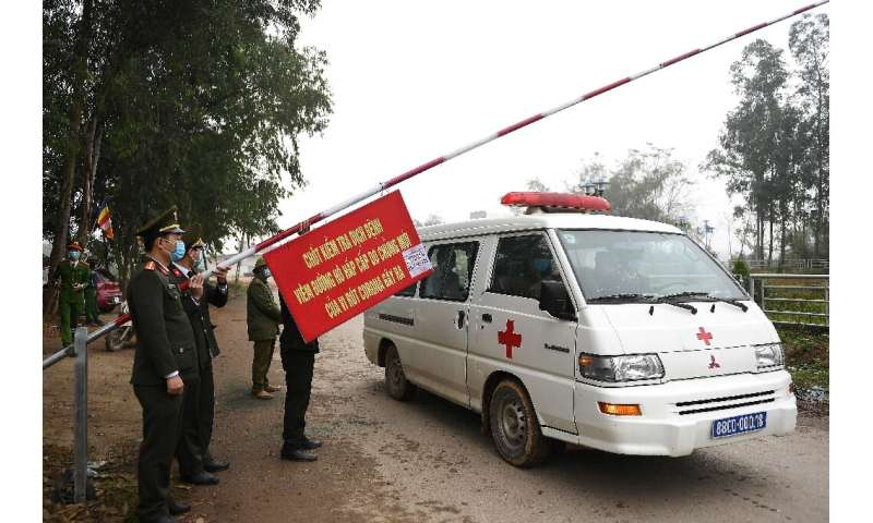 Police allow an ambulance to pass through a checkpoint outside a quarantined area in Vietnam