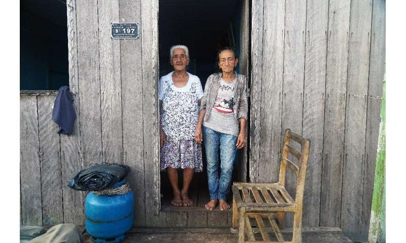 Raimunda Vianam (L), 88, and Maria Conceicao Braga, 76, pose in the town of Carauari where residents fear the reach and spread o