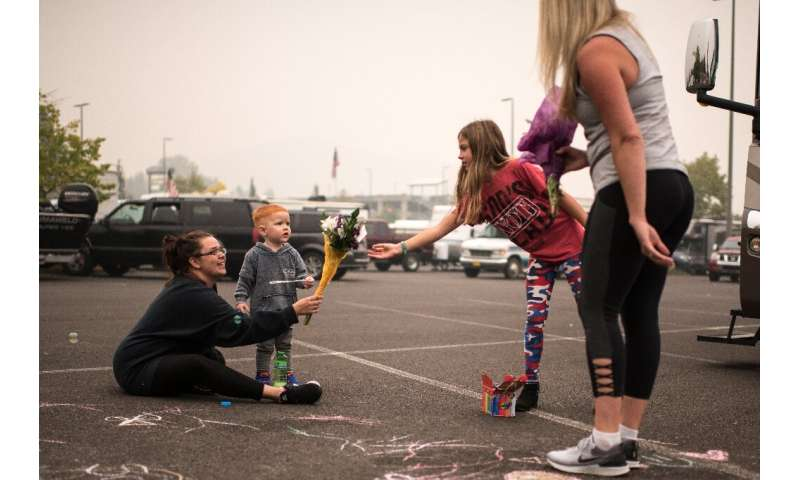 Rebecca Manley and her son, James, accept a bouquet from volunteers handing out flowers at a fire evacuation site set up in the