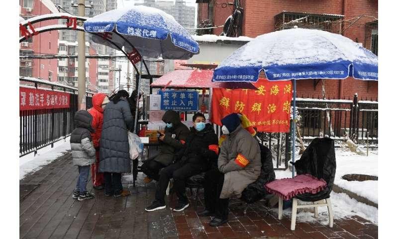 Os moradores monitoram a entrada de um complexo em Pequim.  Alguns bairros estão solicitando aos moradores que leiam um código QR para preencher