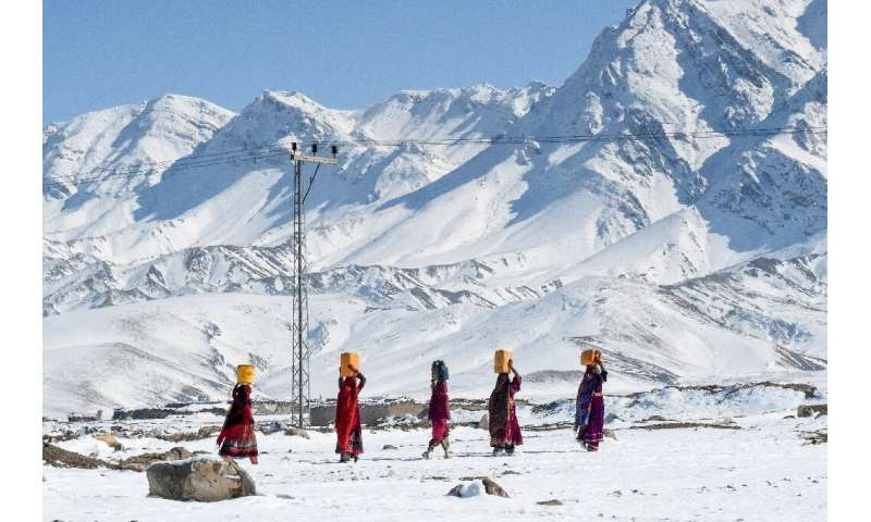 Residents of Khanozai, northwest of Quetta, Pakistan, carry water pots above their heads as they walk home after heavy snowfall