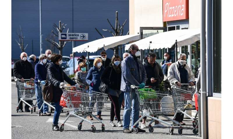 Residents queue up outside a supermarket in Codogno, southeast of Milan