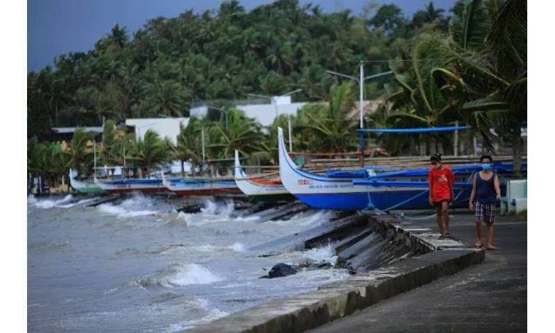 Residents walk past parked wooden boats along a boulevard in Legazpi