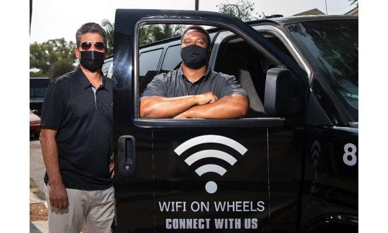 Roman Reyna (Kiri) dan Kevin Watson (Kanan), dari JFK Transportation, berpose di depan salah satu minivan mereka yang memberikan akses wifi kepada anak-anak yang kurang terlayani