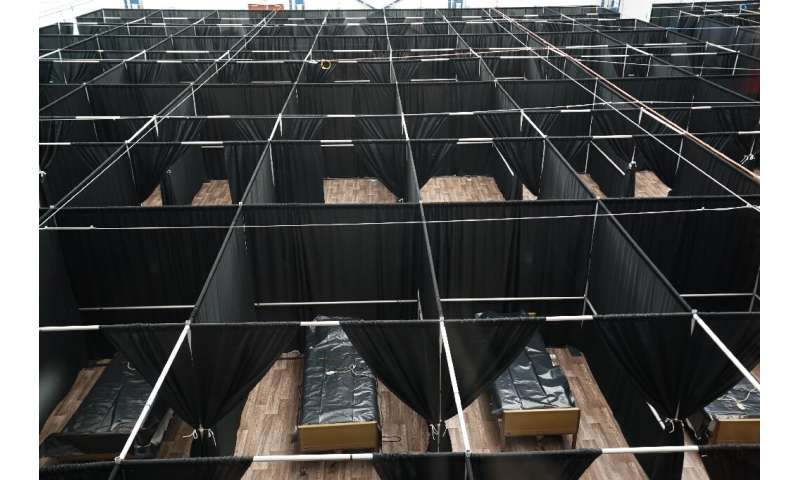 Rows of beds separated by black fabric are set up as a temporary field hospital for COVID-19 patients at the USTA Billie Jean Ki