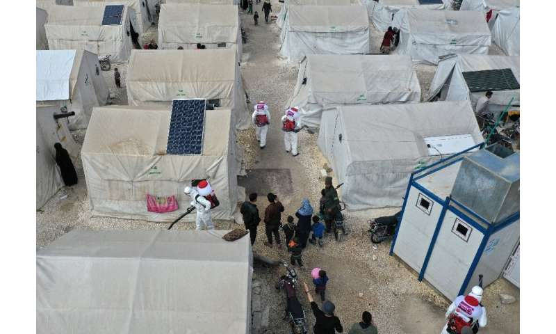 Sanitation workers disinfect a camp for displaced Syrians next to the Idlib municipal stadium