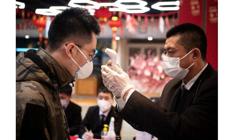 Security personnel check the temperature of shoppers at Hema, an Alibaba supermarket in Hangzhou, the latest city to face restri