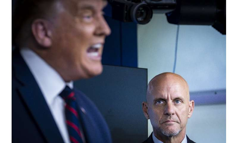 Stephen Hahn, commissioner of the Food and Drug Administration (r) watches as President Donald Trump (l) speaks at the White Hou