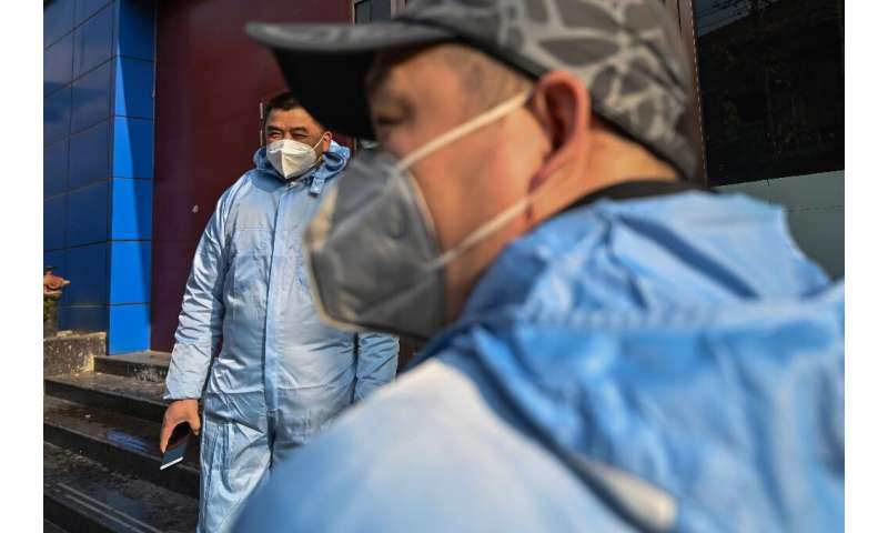 Taxi drivers wearing protective clothing in Wuhan, where the outbreak began