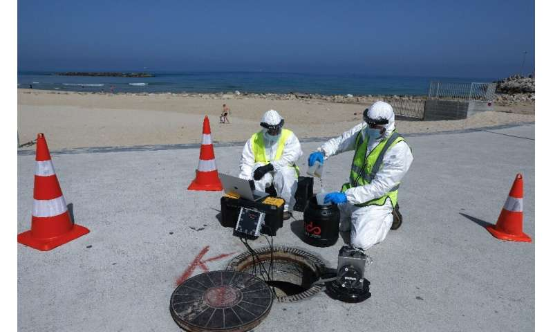 Technicians from Israeli firm Kando extract sewage samples from a manhole near the beach, in the southern coastal Israeli city o