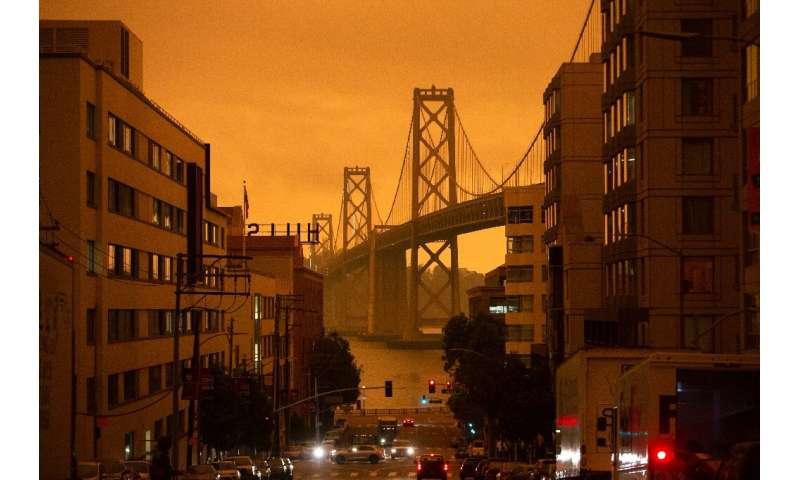 The San Francisco Bay Bridge is seen along Harrison Street under an orange smoke-filled sky in San Francisco, California on Sept